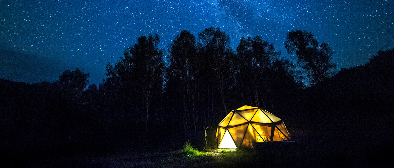 a tent set up under a starry sky