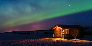 Cabin lit up beneath Northern Lights