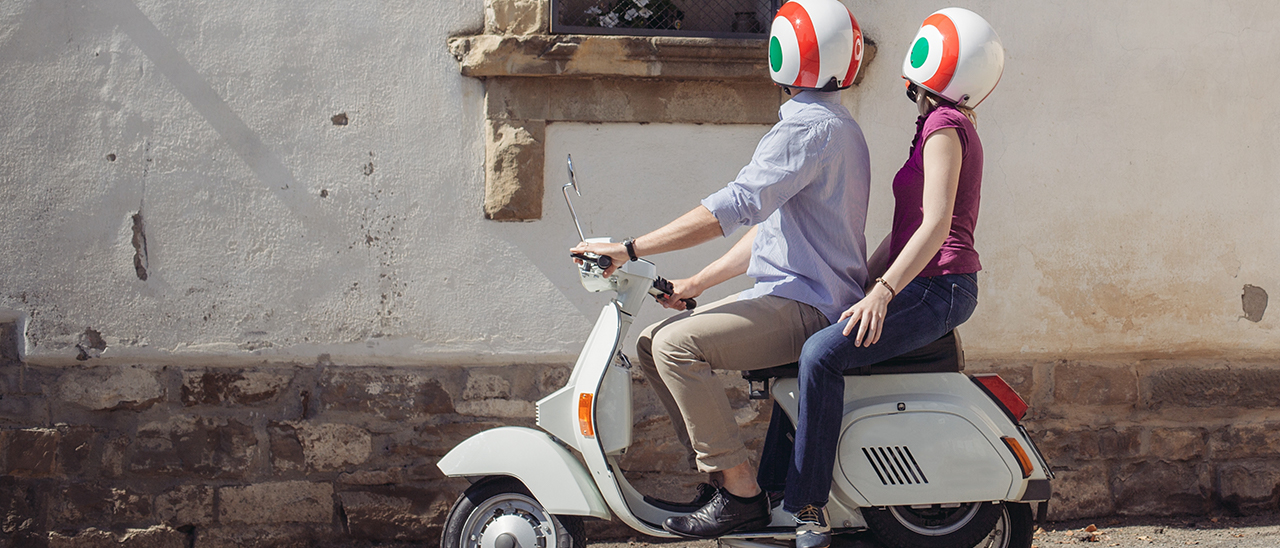 Couple riding a Vespa scooter