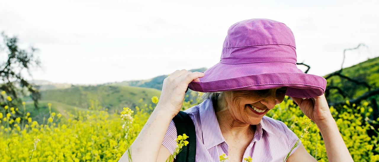 a smiling woman adjusts her hat
