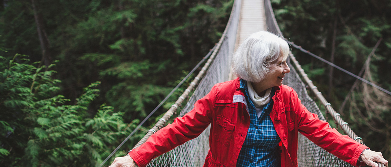 a smiling woman crosses a rope bridge