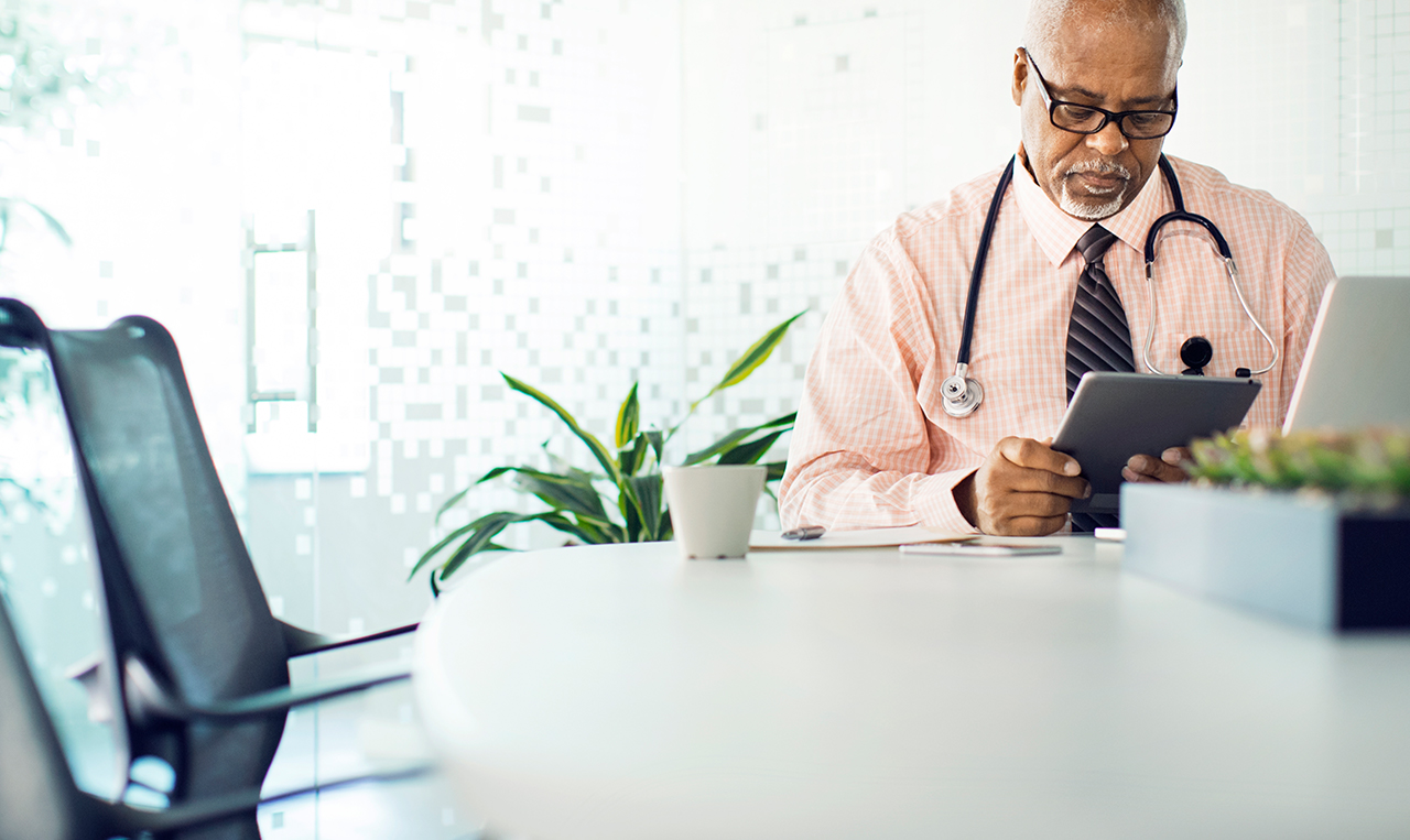 a doctor sits and looks at a tablet