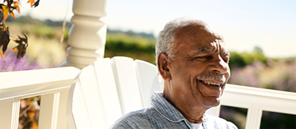 a smiling man sits on a porch