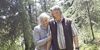 Senior couple embracing as they walk through forest photo